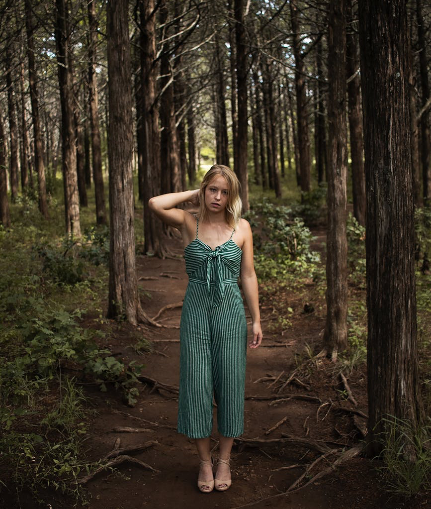 woman standing in the middle of a forest